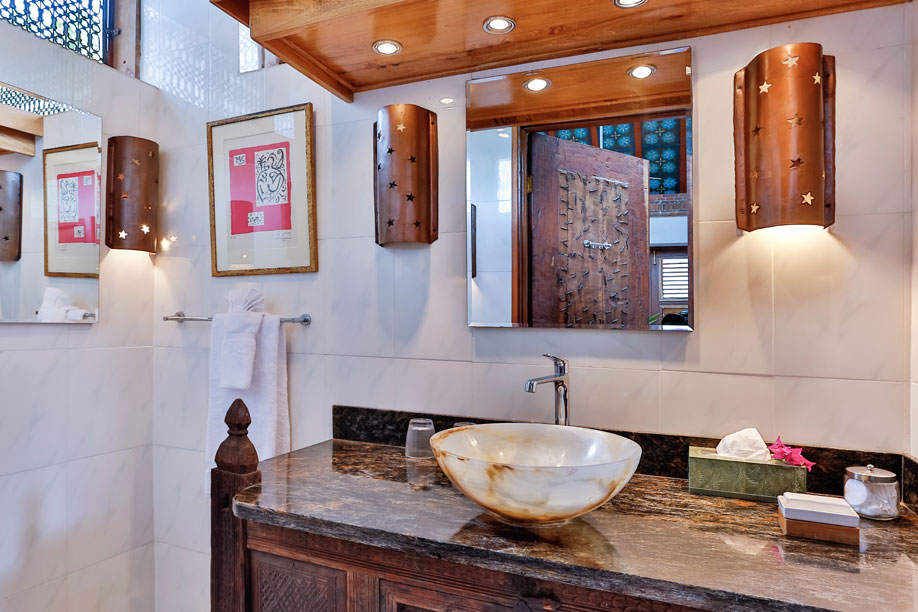 Temple Bathroom with Alabaster Bowl, Granite Counter and Marble Tiled Shower